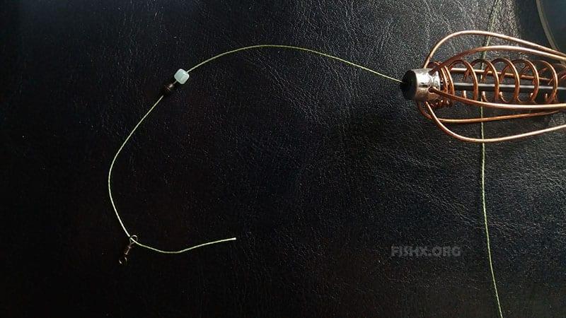 На основной шнур поочередно надевается пружина, бусина, резиновый стопор, вертлюг